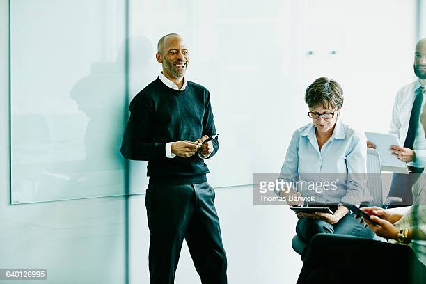 laughing mature businessman in meeting - incidental people stock pictures, royalty-free photos & images