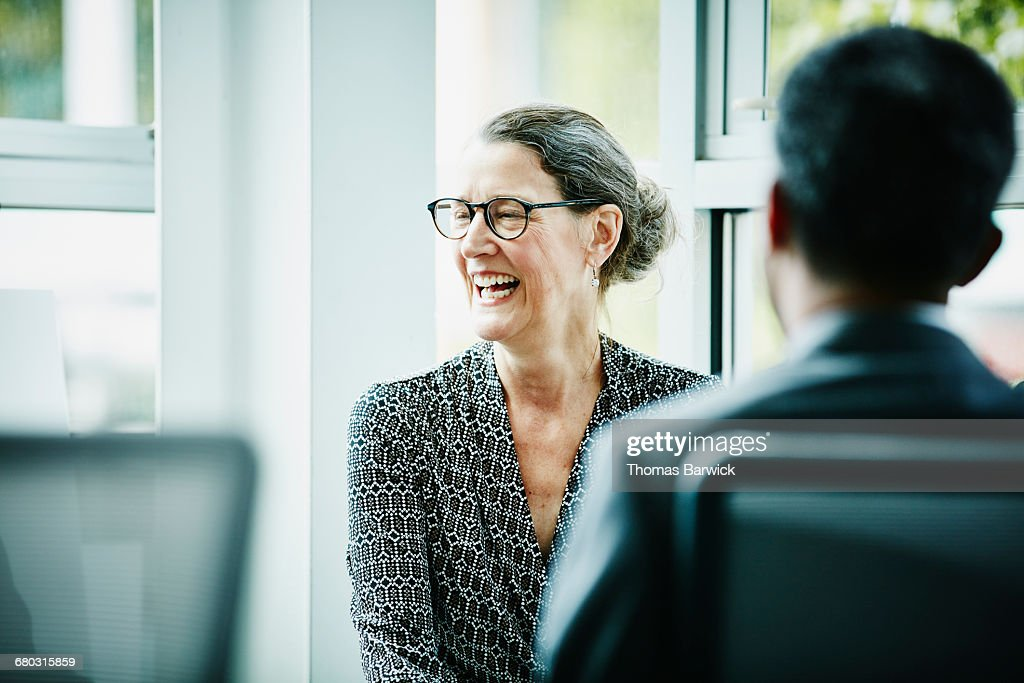 Laughing mature businesswoman in team meeting : Stock Photo