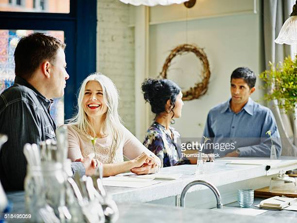 Laughing mature couples standing in restaurant bar