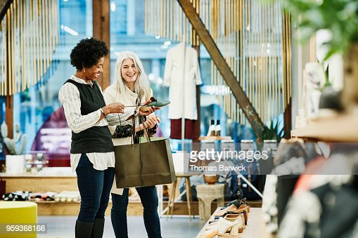 Laughing mature female friends shopping for shoes together in small clothing boutique