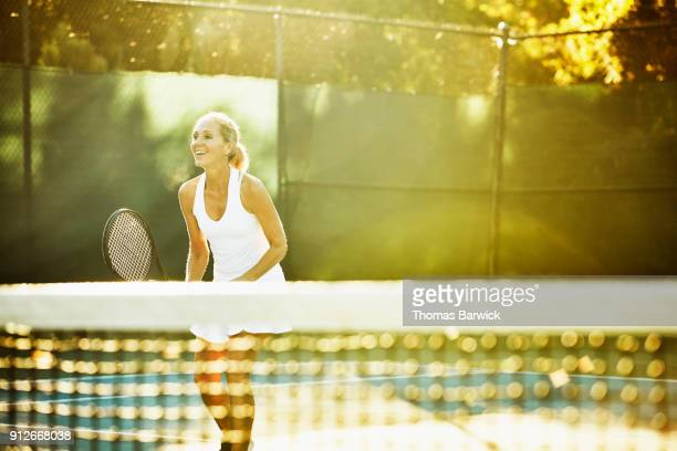 Laughing mature female tennis player at net during early morning workout