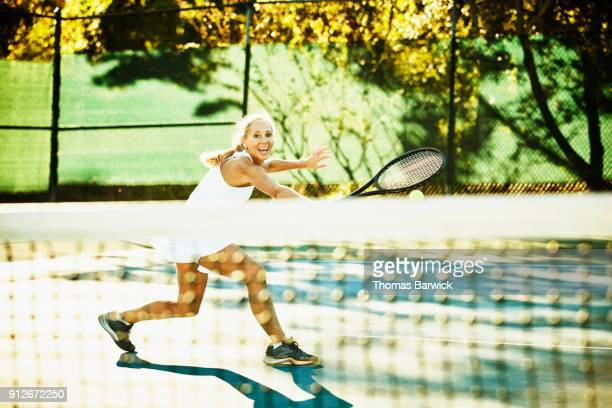 Laughing mature female tennis player hitting backhand return at net during early morning tennis match
