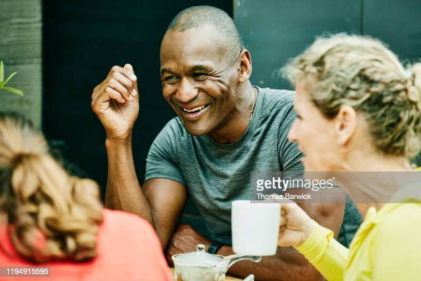 laughing mature friends sitting at outdoor cafe after morning run - khaki green stock pictures, royalty-free photos & images