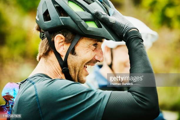 laughing mature man hanging out with friends after mountain bike ride - simple living stock pictures, royalty-free photos & images