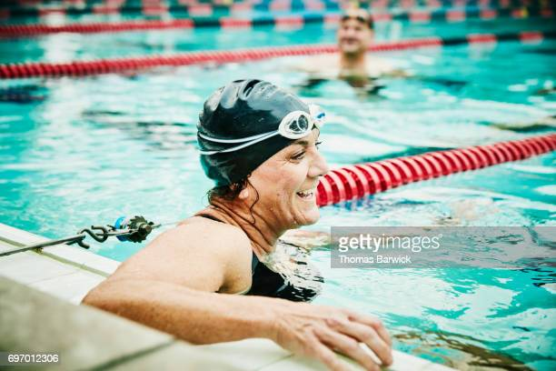 Laughing mature swimmer resting between sets of early morning workout in outdoor pool