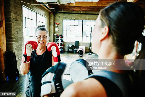 laughing mature woman boxing with coach in gym - sportkleding stock pictures, royalty-free photos & images