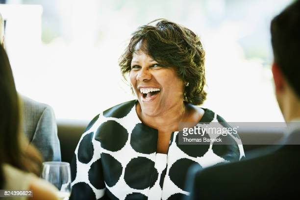 Laughing mature woman dining with friends and family in restaurant