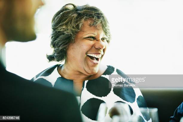 Laughing mature woman in discussion with friends and family during celebration meal in restaurant
