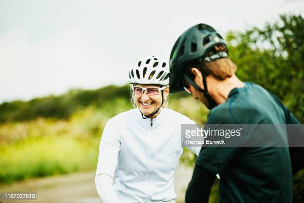laughing mature woman in discussion with friends during mountain bike ride - individuality stock pictures, royalty-free photos & images