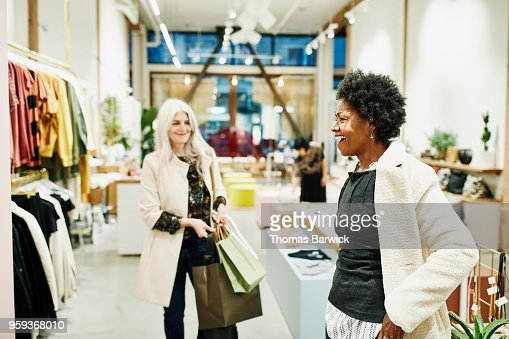 Laughing mature woman trying on coat in clothing boutique while shopping with friend