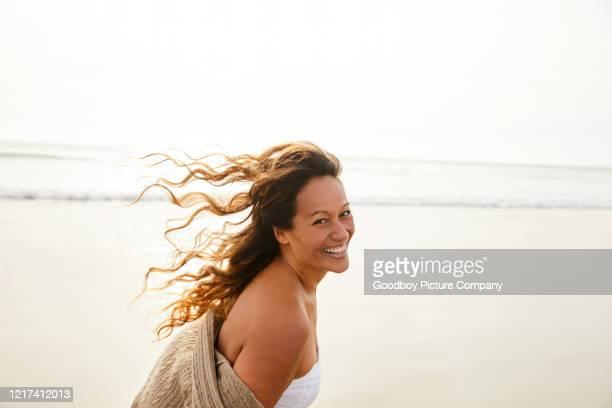 donna matura che ride cammina su una spiaggia in un pomeriggio ventilato - donne mature foto e immagini stock