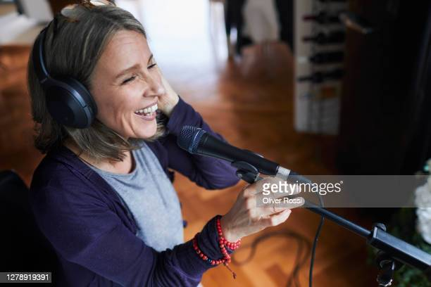 laughing mature woman with headphones and microphone - one mature woman only stock pictures, royalty-free photos & images