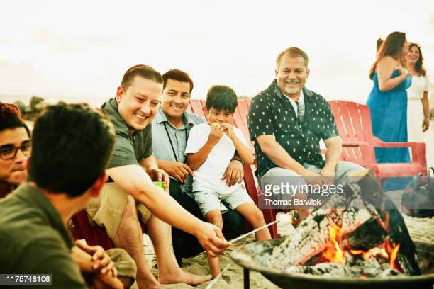 Laughing men hanging out by fire during family beach party