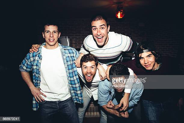 Laughing men posing at party at night
