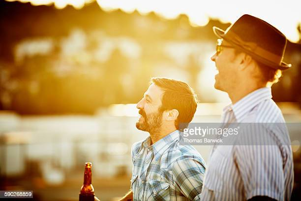 Laughing men sharing beers with friends on rooftop