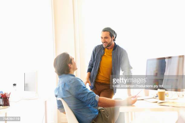 Laughing men talking near computer in office