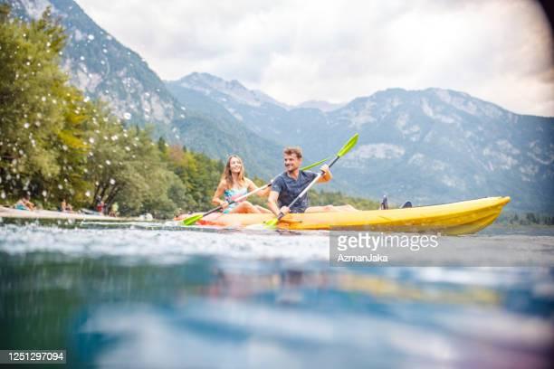 laughing mid adult couple kayaking on vacation in slovenia - adulto de idade mediana imagens e fotografias de stock