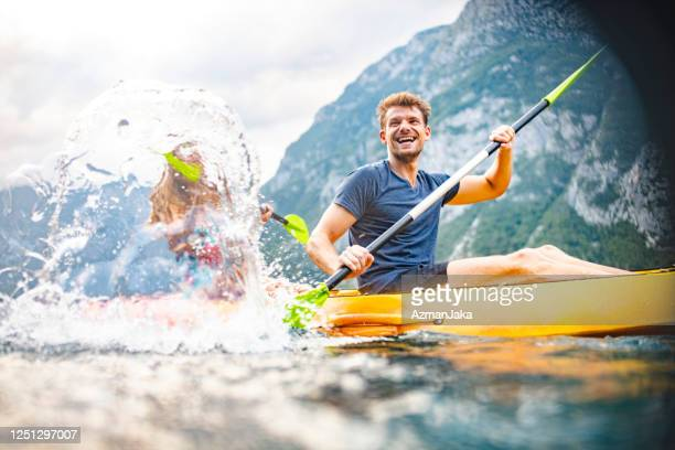 laughing mid adult male kayaker splashing water with paddle - adulto de idade mediana imagens e fotografias de stock