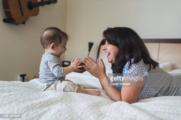 laughing mid-30's mom clapping hands on bed with 1 yr old baby - clapping hands stock pictures, royalty-free photos & images