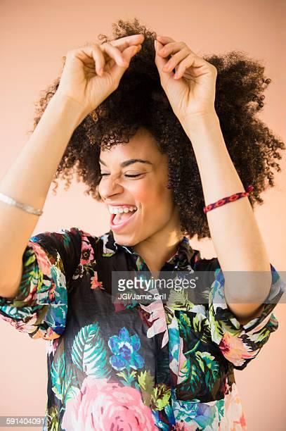 Laughing mixed race woman dancing