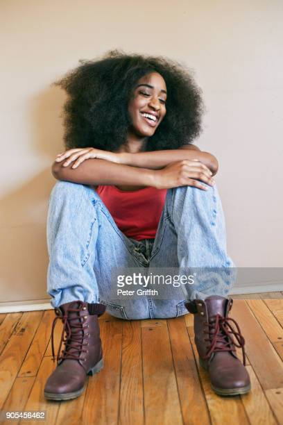 laughing mixed race woman sitting with arms crossed - black boot stock pictures, royalty-free photos & images