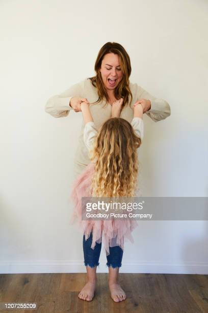 laughing mom holding her little girl in the air while playing at home - innocence stock pictures, royalty-free photos & images