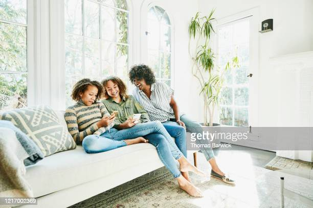 laughing mother and daughters sitting on couch in living room looking at smartphone - ragazzine scalze foto e immagini stock