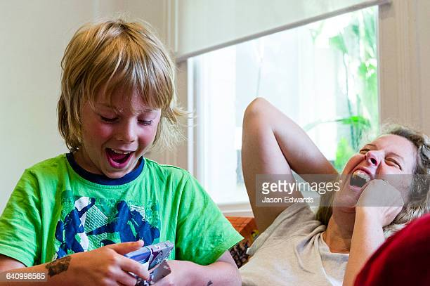 A laughing mother and son open gifts on Christmas morning.