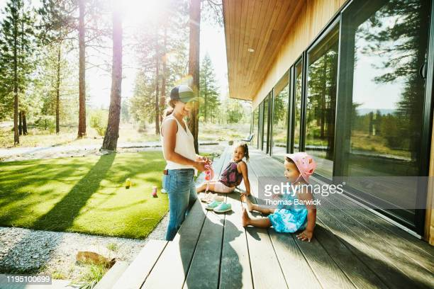 laughing mother hanging out with young daughters on front porch of vacation home on summer afternoon - holiday villa stock pictures, royalty-free photos & images