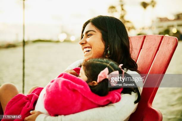 Laughing mother holding daughter wrapped in blanket in lap during family beach party
