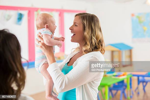 Laughing mother holding her sweet infant baby girl in daycare