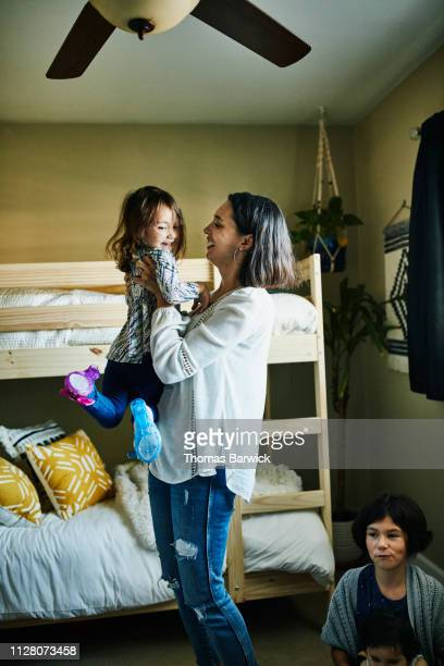 Laughing mother lifting up smiling young daughter in bedroom