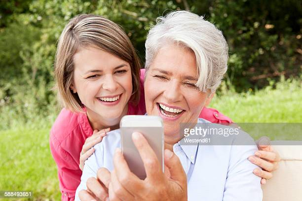 Laughing mother with adult daughter looking at cell phone outdoors