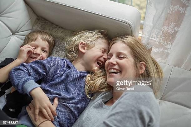 Laughing mother with two sons on couch