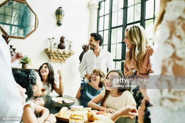 Laughing multigenerational family gathered around dining room table sharing appetizers before birthday dinner
