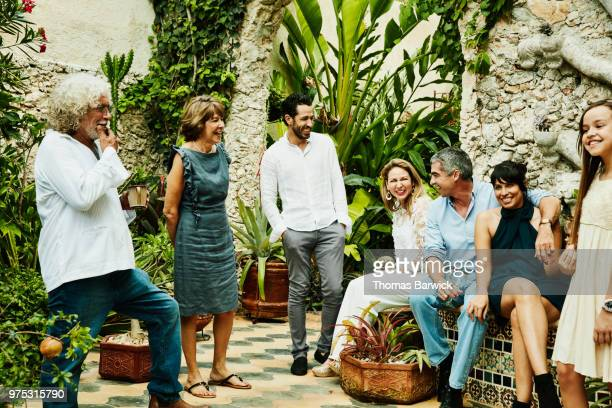 Laughing multigenerational family in discussion in backyard garden during dinner party