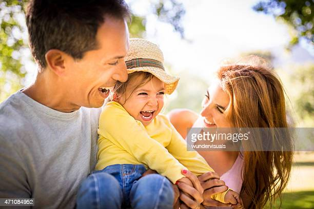 Laughing parents playing with their little girl in the park