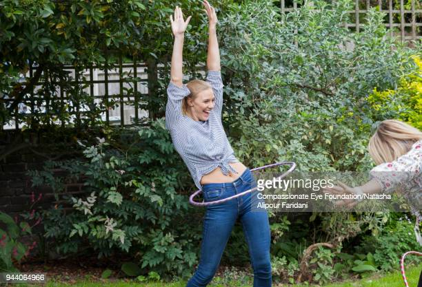 laughing playful woman spinning in plastic hoop in garden - dreiviertelansicht stock-fotos und bilder