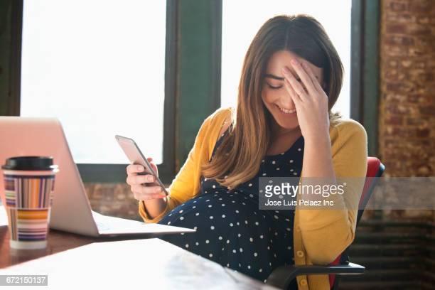 laughing pregnant caucasian businesswoman using cell phone - grossesse humour photos et images de collection