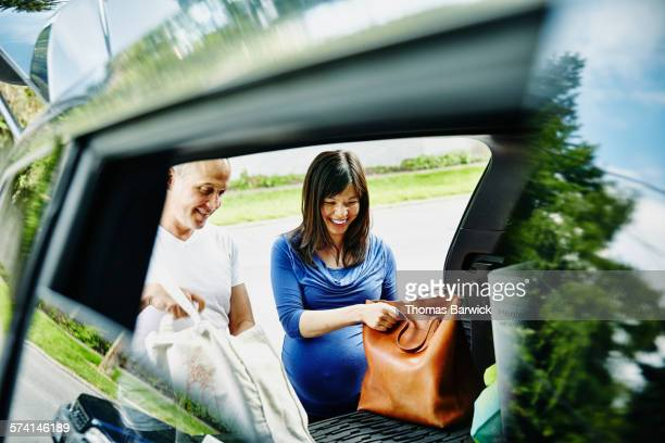Laughing pregnant couple unpacking trunk of car
