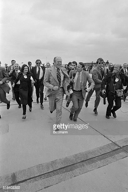 A laughing President Ford leads the White House Press on a chase back to the plane as he avoids responding to questions about Vietnam The President...