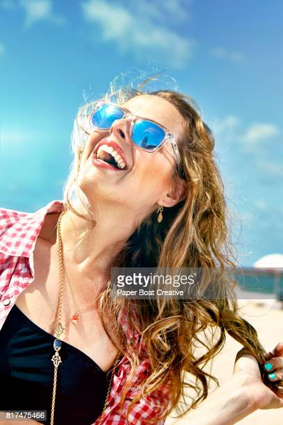 laughing pretty young woman in sunglasses at the beach on a bright day summer