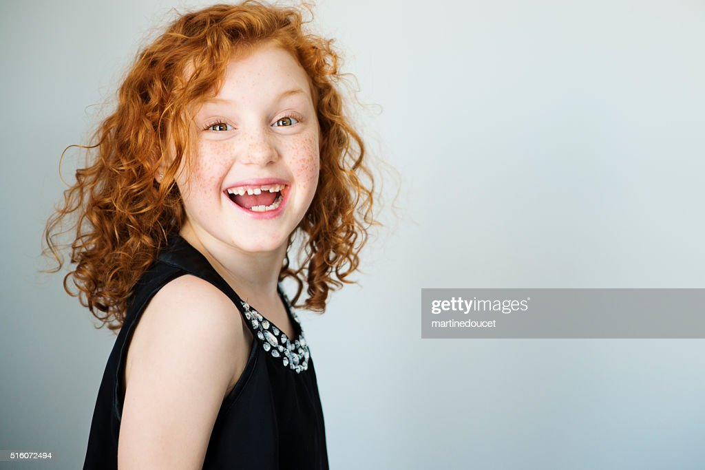 Laughing redhead little girl with freckles and missing tooth. : Stock Photo