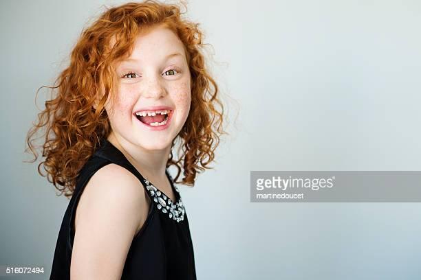 Lachend Rotes Haar kleines Mädchen mit Sommersprossen und fehlende Zahn.
