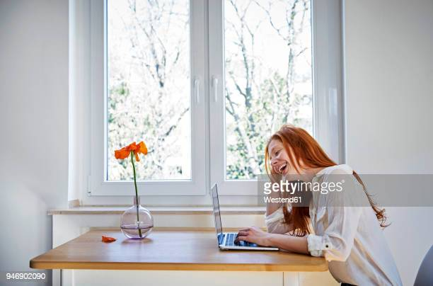 laughing redheaded woman sitting at table in front of window using laptop - mohn pflanze stock-fotos und bilder