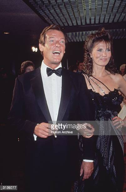 A laughing Roger Moore arrives at the premiere of the James Bond film 'Octopussy' with his costar Swedish actress Maud Adams