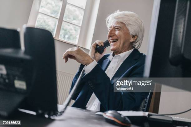 Laughing senior businessman on the phone in his office