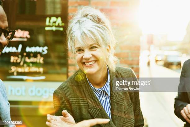 laughing senior businesswoman in discussion while friends during morning commute - midsection stock pictures, royalty-free photos & images