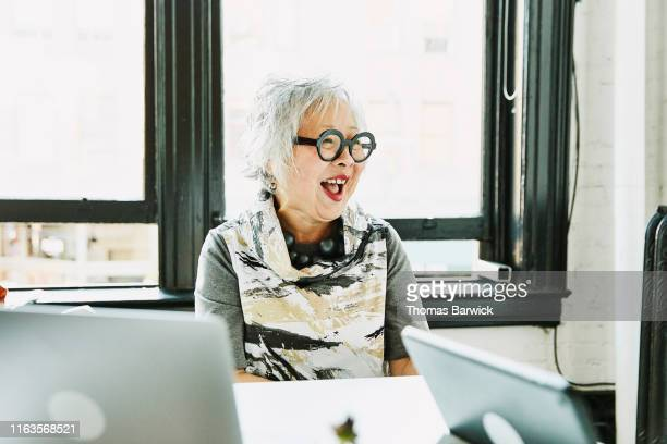 laughing senior businesswoman in meeting in office conference room - disruptaging stock pictures, royalty-free photos & images