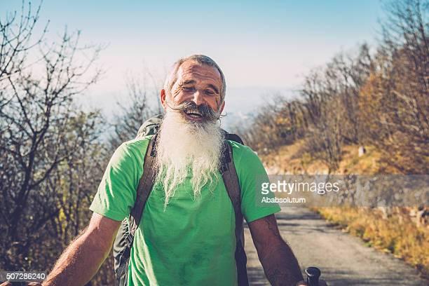 Riendo caucásico Parapente Senior caminando en la carretera de montaña, de los Alpes, Europa